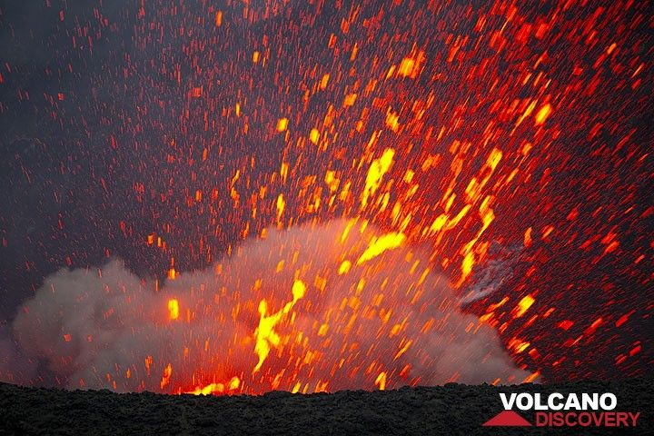 Another violent explosion accompanied by a loud detonation throws out a jet of very fluid lava bursting into bright glowing spatter. (Photo: Tom Pfeiffer)