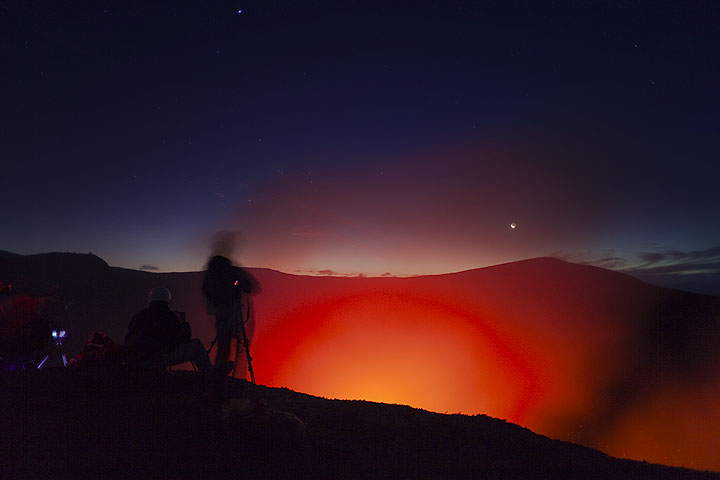 Silhouette of a volcano observer at Yasur with the setting moon. (Photo: Tom Pfeiffer)