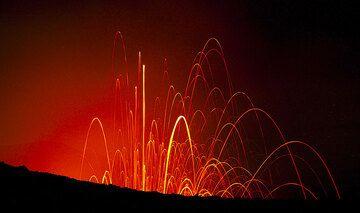 Leutspuren von ausgeworfenen Lavabomben bei Nacht. (Photo: Tom Pfeiffer)
