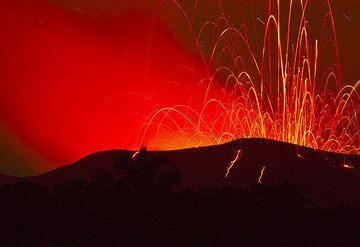 Le Yasur avec une explosion plus forte qui jette beaucoup de bombes au dehors du cratère sur les pentes extérieurs. (Photo: Tom Pfeiffer)