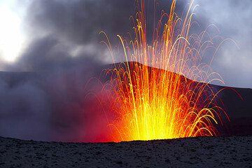 Wenn es dunkler wird, erlauben Langzeitbelichtungen, die parabolischen Flugbahnen der Bomben abzubilden, die mehr als 200 m über den Kraterrand hoch ausgeworfen werden. (Photo: Tom Pfeiffer)