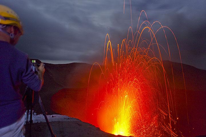 Photographer filming Yasur volcano in the evening. (Photo: Tom Pfeiffer)