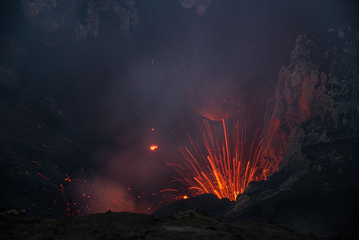 Small eruption of the south vent in the south crater. A narrow glowing hole is seen in the center of the image; this vent only erupted once during 3 days of observation. (Photo: Tom Pfeiffer)