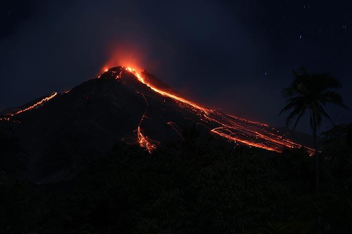 Gunung Karangtang (South Crater) with active lava flows. View From A Hillside Above Winangun Village, Siau Island, North Maluku, Indonesia