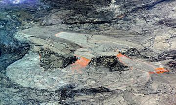 This close-up view of the active western portion of the Halema'uma'u lava lake at the summit of Kīlauea was captured on Thursday, May 6 through the lens of a laser rangefinder used by HVO scientists to measure distances to features within the crater. HVO scientists observed that the area immediately surrounding the inlet to the lava lake (above-center) was slightly perched relative to the rest of the active surface, and it was intermittently feeding lava channels to lower-lying parts of the lake (below-center and below-right). The western fissure is out-of-view to the upper-left and the main island in the lava lake is out-of-view to the right. USGS caption & image (color corrected).