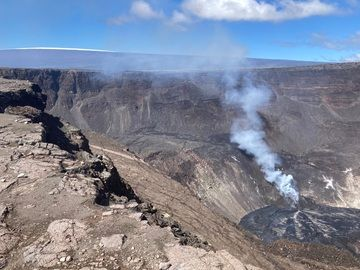 Western fissure emits the gas content and supplies the lava flow into the lava lake. Snow from a recent storm can be seen on the summit of Mauna Loa Volcano, in the upper left corner of the image (image: HVO)