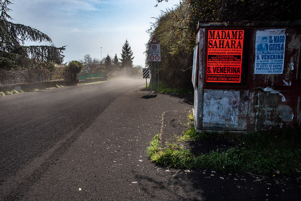 Ash-covered street and ads from local magicians ready to help (image: Tom Pfeiffer / VolcanoDiscovery)