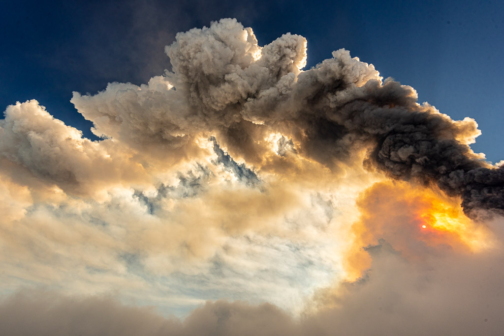 Golden sunlight filtered by volcanic ash and gasses with the eruption plume (image: Tom Pfeiffer / VolcanoDiscovery)
