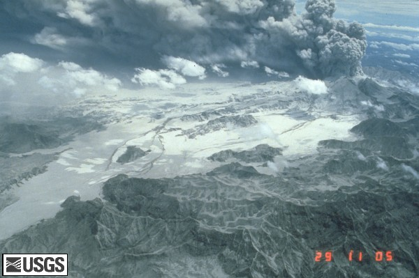 The June 29, 1991 eruption column from Mount Pinatubo with Marella River Valley. Aerial view to north of pyroclastic-flow deposits in Marella River valley (in foreground) and tributaries of Balin Buquero River (in distance) with ash plume rising from Pinatubo's caldera. Pyroclastic-flow deposits to east of isolated hill in right center as about 200 meters thick. Dark streaks on pyroclastic-flow deposits are lahar deposits generated by rains. U.S. Geological Survey Photograph taken on June 29, 1991, by Ed Wolfe.