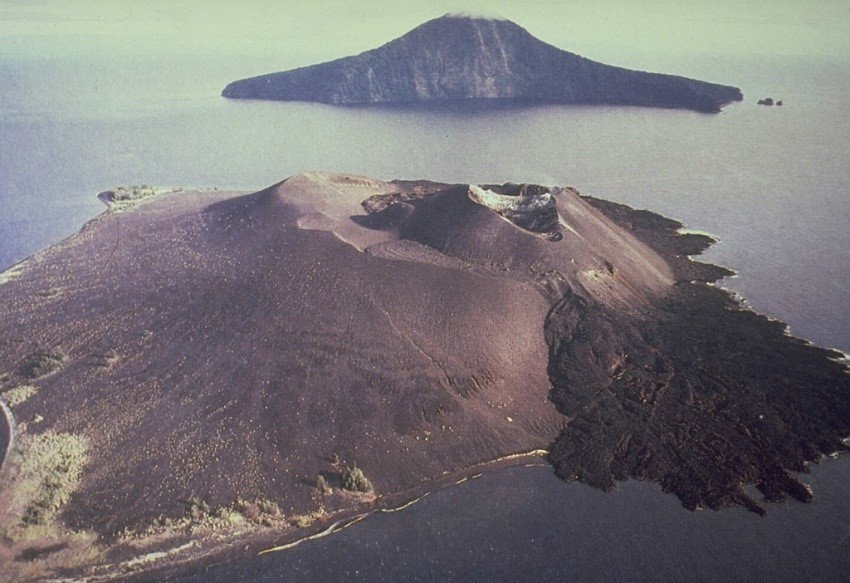 The 1883 eruption destroyed much of Krakatau Island, forming a submarine caldera. Rakata Island in the background is the truncated rim of the 1883 caldera and Anak Krakatau in the foreground is a post-caldera cone that first emerged from the sea in 1929 and has been frequently activity since (Image: Volcanological Survey of Indonesia).