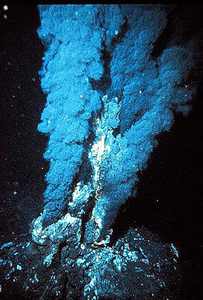 """Black smoker from the mid-Atlantic Ridge -- These dark, billowing clouds of hot hydrothermal fluid are rich in dissolved metals. As they rise into the cool ocean water, they precipitate these metals along the sides of the vent, thus creating a """"chimney"""" that builds over time. The fluids also provide nutrients to a variety of unusual plants and animals that congregate around the vents in an area of the ocean where life would generally not exist. Courtesy of Peter Rona, NOAA."""