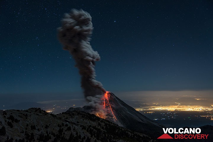 Archive photograph showing explosive activity of Colima volcano in February 2015, with the city lights of Colima in the background.