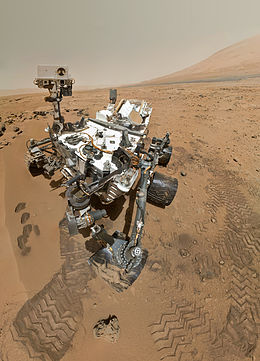 Curiosity rover in Gale Crater, on Mars, collecting a dusty lava bomb sample. Outer slopes of Mt Olympus volcano in background (October 31, 2012, NASA image)