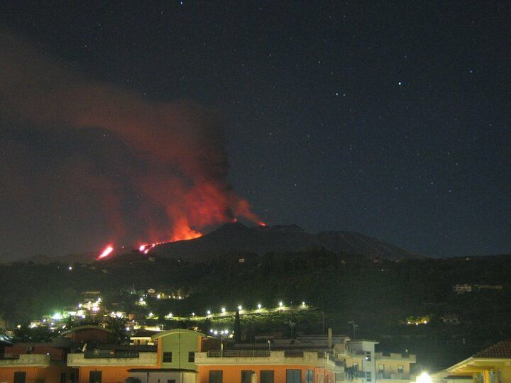 Etna's lava flows descending into Valle del Bove; strombolian activity from the New SE cone (c) and strong glow from Voragine summit crater (r) (image: Osservatorio Meteorologico Nunziata webcam, view from E)