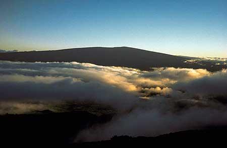 Mauna Loa, der größte aktive Vulkan der Erde. Seine flache Siluette erhebt sich über die Wolken.