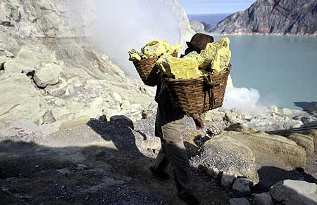 Sulfur miner at Ijen volcano carrying baskets of solid sulfur up from the crater.