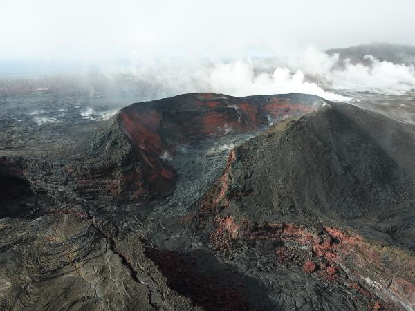 Crusted cone and channel of Fissure 8, primary vent of recent eruption. Steaming caused by rainfall. Credit: USGS.