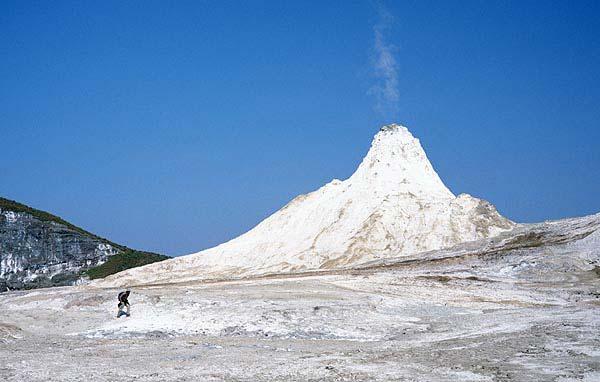 "Verwitterte Natronkarbonat-Lava und ein steiler Vulkankegel, sogenannter ""Hornito"""