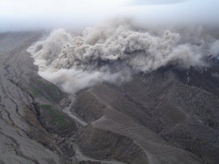"A Pyroclastic flow ""boils"" into the upper reaches of Tyres Ghaut, on the northwestern side of the  Soufriere Hills Volcano. Picture taken at 11:24 (local time) 3 January 2007, courtesy of Greg Scott of Caribbean Helicopters."