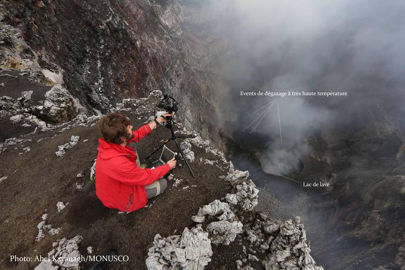 Nyamuragira's pit crater with a small lava lake observed on 27 April 2016; volcanologist Sebastien Valade takes thermal measurements from the rim. (Image: MONUSCO via Culture Volcan)