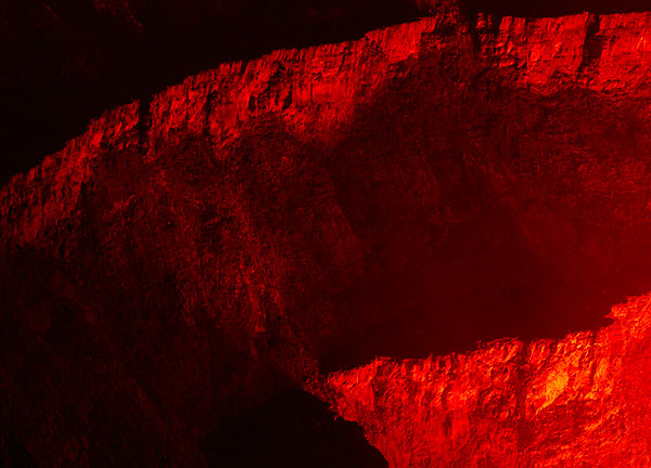 The vertical walls of the inner crater illuminated by the red light from the lake