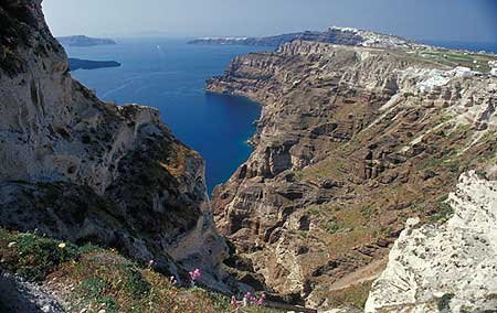 The present-day caldera of Santorini with the white Minoan deposit visible as the thick topmost layer in the cliffs.