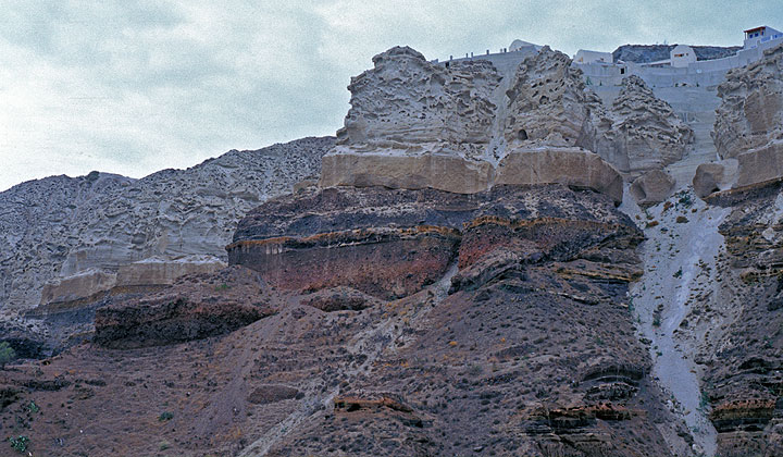 The caldera cliffs near the site looking north; the Minoan deposit is the thick topmost layer including a 5 m thick base of fall-out pumice. Construction is consuming the pumice layer from top down, and destroying important geological features visible in the wall.