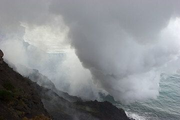 A thick plume of steam rises from the entry point of the lava flow.