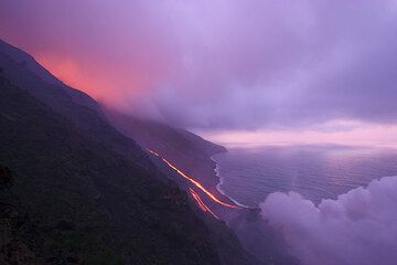 Glow from the lava flow illuminating the cloud cover on the mountain.