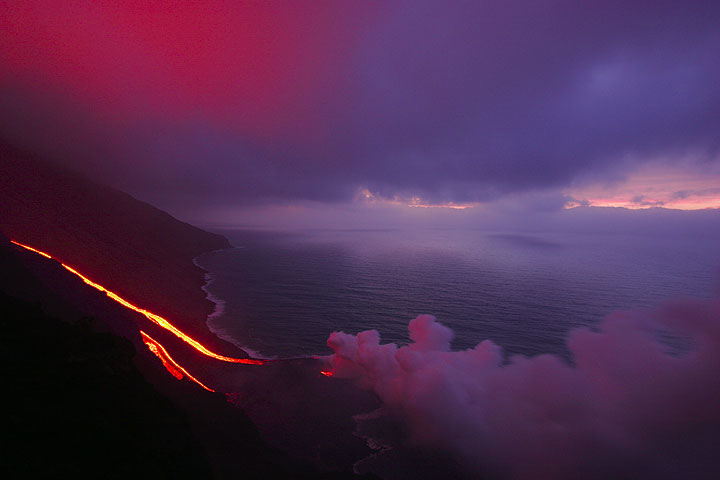 The lava flows in the twilight and white mist over the sea.