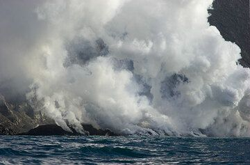 Steam from the lava fronts in the sea.