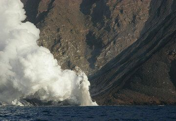Small littoral explosions occur sometimes where the active flow meets the sea; fragments and boiling water are thrown into the air, leaving steam trails.