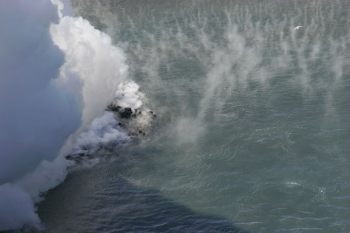 Steaming sea water surrounding the new land