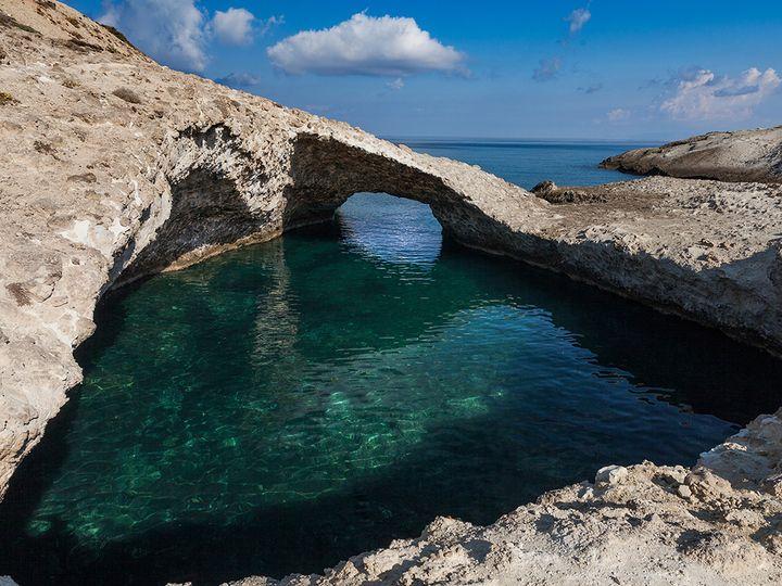 Eine Bucht und eine natürliche Brücke darüber haben sich im vulkanischen Tuff gebildet.