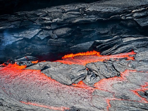 Liquid red hot lava and pieces of cooled black crust plunging down into a cavity on one side of the lava lake (Stefan Tommasini - January 2018)
