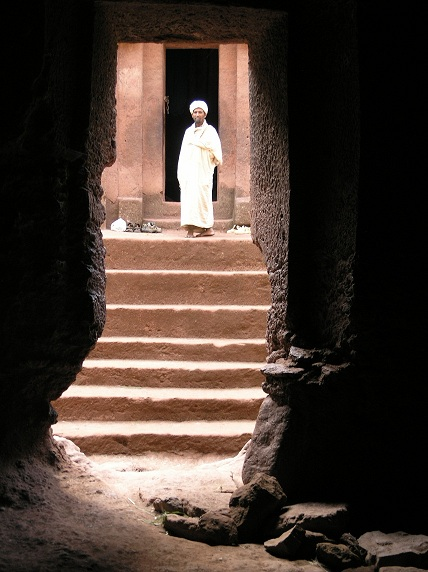 Ethiopian orthodox priest at the entrance of a ca 900 year old rock hewn church