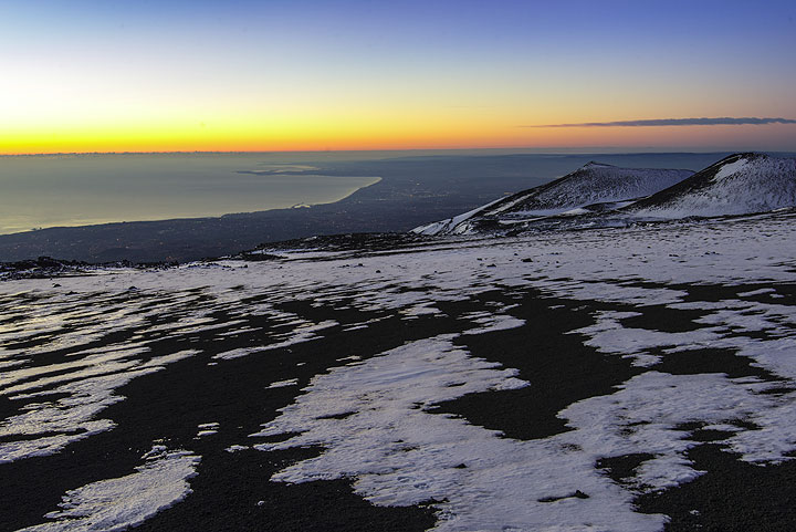 Sunrise over the bay of Catania seen from the snow covered slopes of Mt Etna