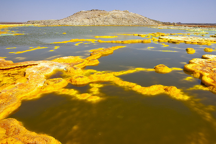 The Dallol salt dome with a foreground of dark green acid ponds with yellow ´salt cakes´ (Dec 2010; image: Tom Pfeiffer)