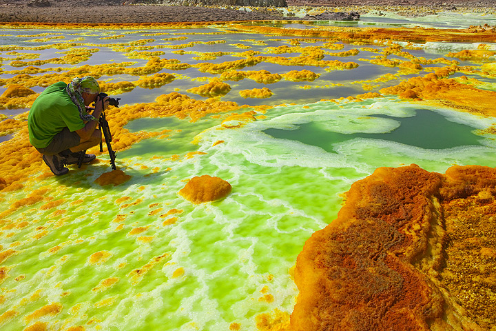 Photographing the abundant green acid ponds amidst the white-yellow-orange salt deposits (Dec 2010; image: Tom Pfeiffer)