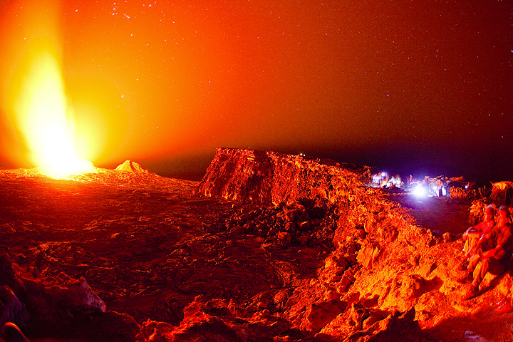 Strong nighttime glow of the active lava lake as seen from the caldera rim (bluish lights to the right are observers at Erta Ale camp site) (Dec 2010; image: Tom Pfeiffer)