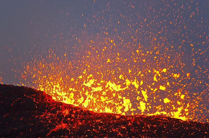 A large lava bubble explodes at the surface of the full lava lake (Dec 2010; image: Tom Pfeiffer)