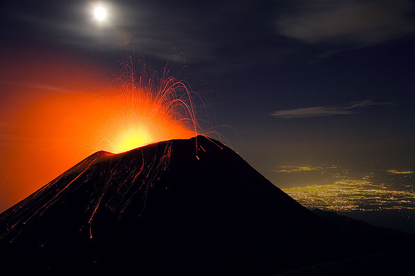Mt Etna in eruption under a full moon and the city lights of Catania