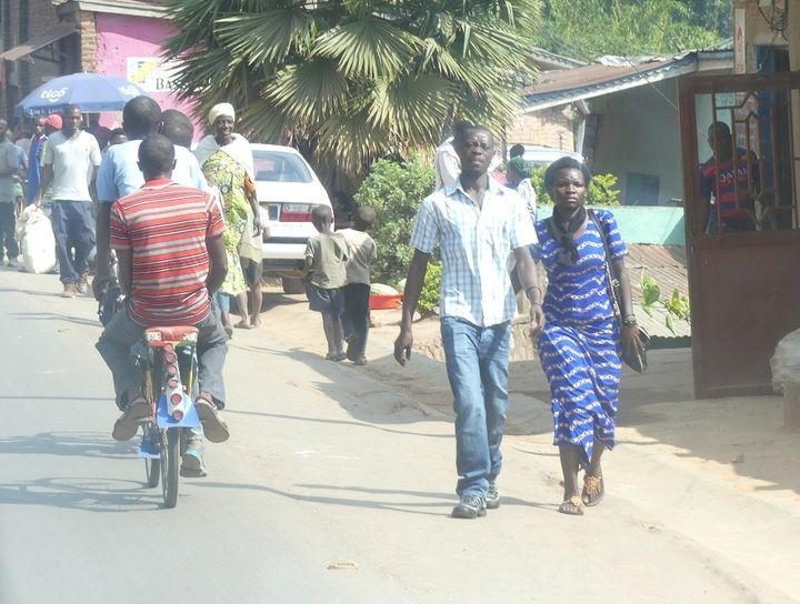 Hustle and bustle of Kigali city with many bike taxis and pedestrians