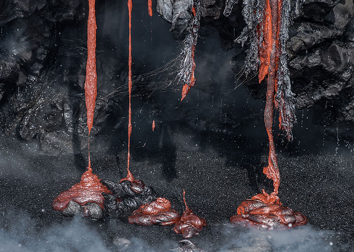 Lava dripping onto the black sand shoreline