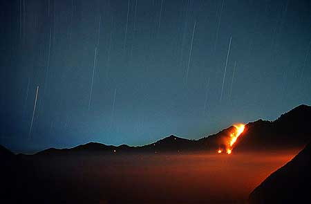 Nighttime view onto the Tengger caldera with forest fire on the caldera wall