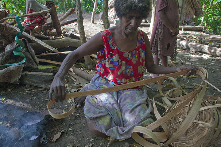 A woman in a local village dyeing bands from banana leaves