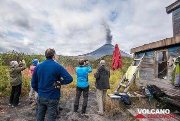 Group observing Karymsky volcano erupting