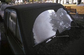 Ash fall colvering the wind shield of a car