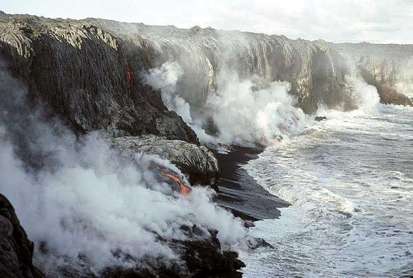 Ein Lava-Bank in Bildung: aktive Lavaströme über einen kleinen Strand, bilden eine solide Cap.