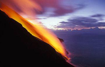Lava flow on Stromboli volcano flowing down the Sciara del Fuoco and entering the sea